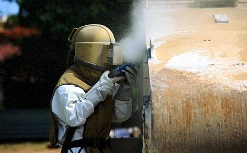 Man Sawing a Wall with Dust Coming Off