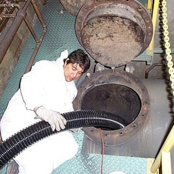 Man Vacuuming Contaminants out of Hole