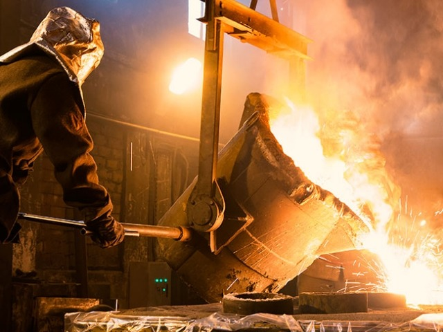 Foundry worker pouring melted metal into molds