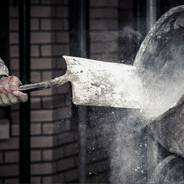 Shovel hitting concrete mixer with dust coming off